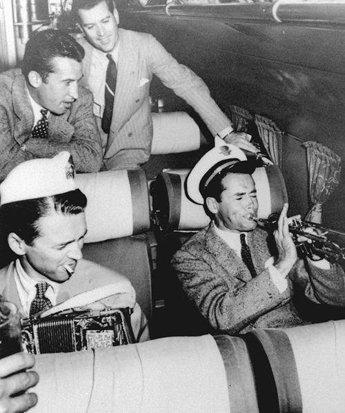 Actors Jimmy Stewart (with accordion) and Henry Fonda (with trumpet) making music during airline flight. (Photo by John Swope//Time Life Pictures/Getty Images)