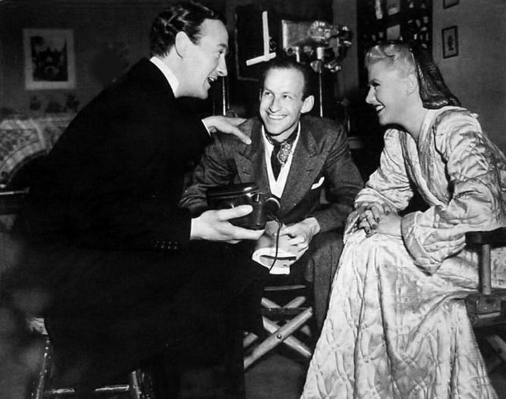 Director Garson Kanin, center, shares a lighthearted moment with his stars David Niven and Ginger Rogers on BACHELOR MOTHER (1939)